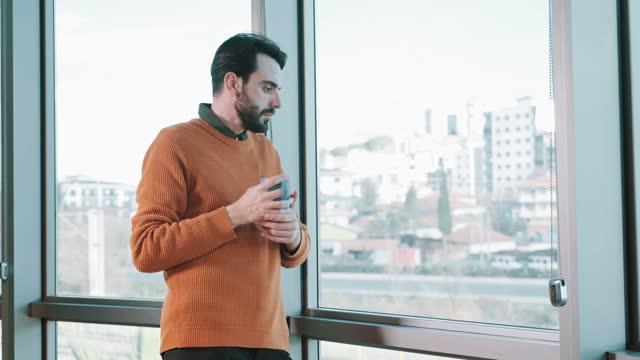 vídeos de stock, filmes e b-roll de empresário parado perto da janela e bebendo café - café bebida