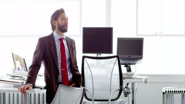 ms businessman standing in discussion at table in office workstation - ein mann allein stock-videos und b-roll-filmmaterial
