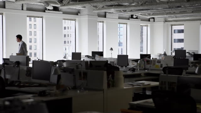 vidéos et rushes de ms pan businessman standing in empty office looking out window/seattle, washington, usa - 10 secondes et plus