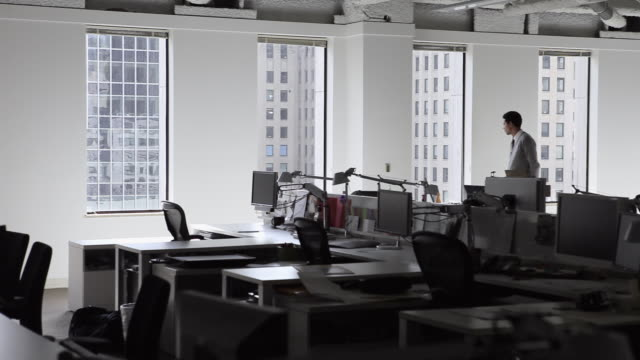 ms pan businessman standing in empty office looking out window/seattle, washington, usa - medium shot stock videos & royalty-free footage