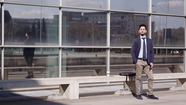 vidéos et rushes de businessman standing in front of modern building enjoying the sun - barbe