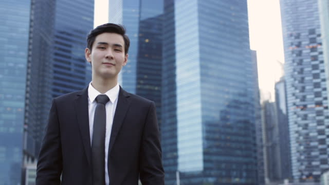 MS Businessman standing in front of skyscrapers.