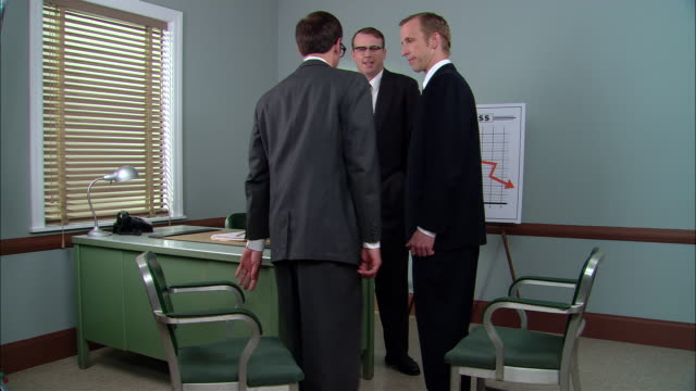 stockvideo's en b-roll-footage met ms businessman standing in office near loss graph as two men walk in and sit down/ boss talking and appearing angry/ new york city - graph