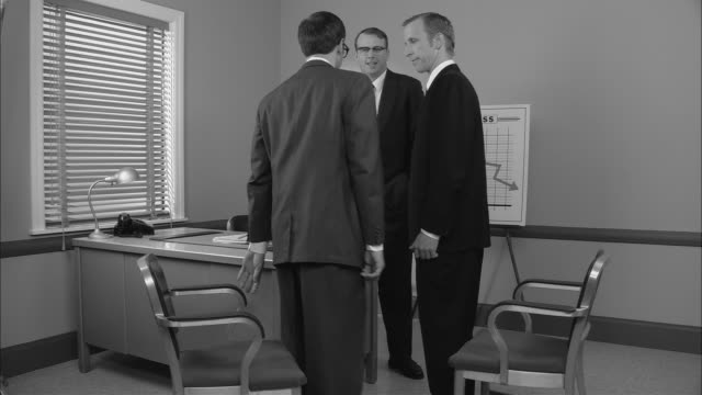 B/W MS Businessman standing in office near Loss graph as two men walk in and sit down/ Boss talking and appearing angry/ New York City