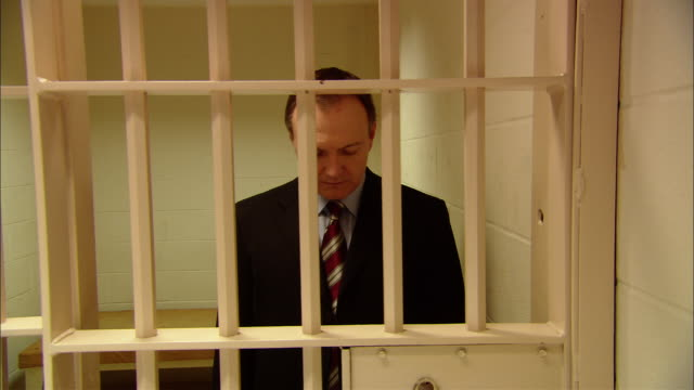 MS Businessman standing in prison cell, looking down as door closes/ New Jersey