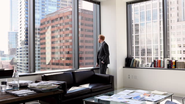 ws businessman standing looking out window in corner office - one man only stock videos & royalty-free footage