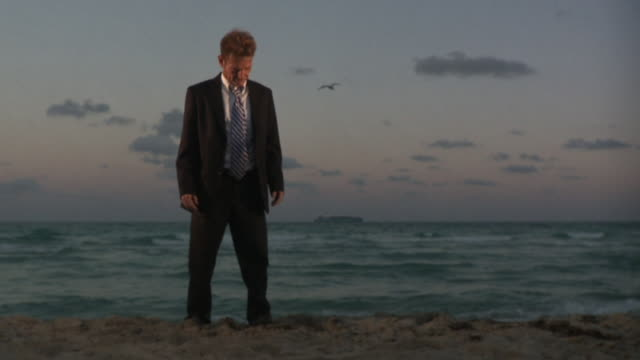 ws slo mo businessman standing on beach / south beach, florida, usa - disappointment stock videos & royalty-free footage
