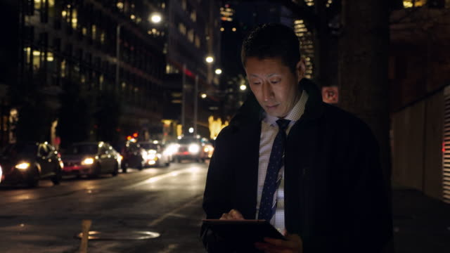 vidéos et rushes de ms businessman standing on city street at night while working on digital tablet - temps limité