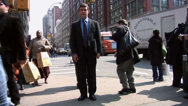 TL WS businessman standing on corner of 6th Avenue and 23rd Street as people and traffic move past him/ New York City
