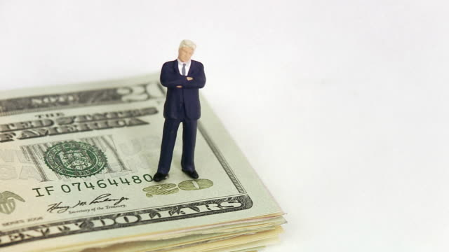 Businessman standing on dollar bills.