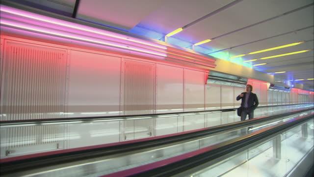 vídeos de stock, filmes e b-roll de ws businessman standing on moving walkway in airport / munich, germany - bolsa tiracolo bolsa