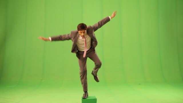 businessman standing on one leg  - farbiger hintergrund stock-videos und b-roll-filmmaterial