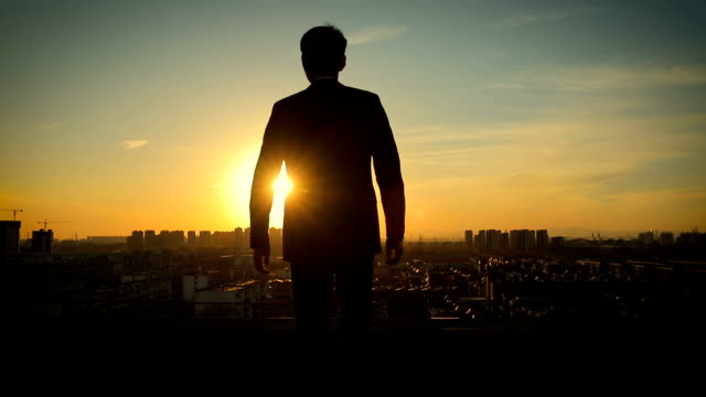 Businessman standing on roof with arm raised at sunset