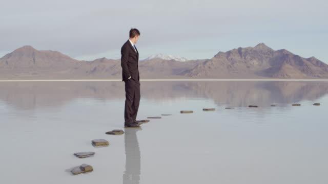 stockvideo's en b-roll-footage met ms pan businessman standing on stone pathway in lake - de volgende stap