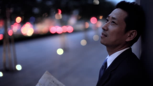 MH LD Businessman Standing on Street Looking Up at Night / Singapore