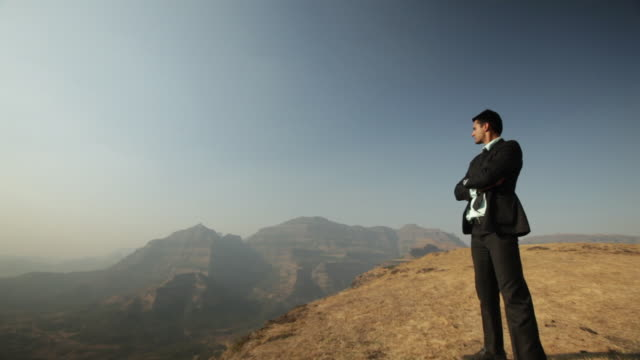 businessman standing on the cliff of mountain with his arms crossed  - aiming stock videos and b-roll footage