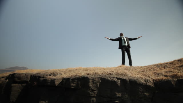 Businessman standing on the cliff of mountain with his arms outstretched