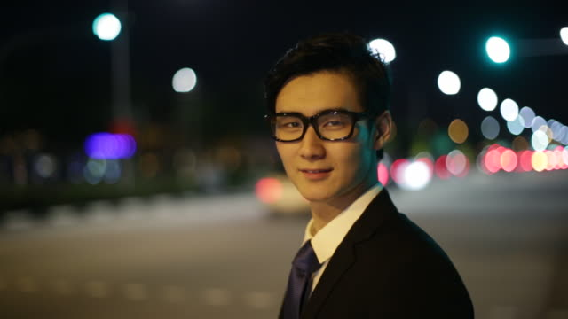 CU Businessman standing on the street at night.