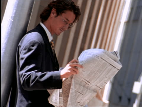 businessman standing outdoors + reading newspaper - one mid adult man only stock videos & royalty-free footage