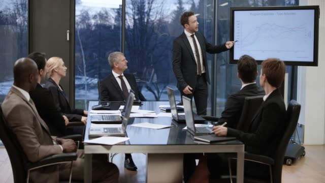 businessman standing up in the meeting room and starting his presentation - explaining stock videos & royalty-free footage