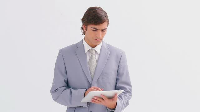 vídeos de stock e filmes b-roll de businessman standing while using a tablet pc - só um rapaz