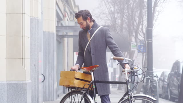 ms businessman standing with bike on sidewalk outside of office building putting on helmet and riding away - cycling helmet stock videos & royalty-free footage