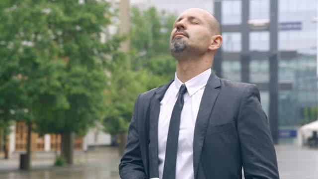 vídeos de stock, filmes e b-roll de slo mo empresário de pé com os olhos fechados no meio de uma praça da cidade - exercício respiratório