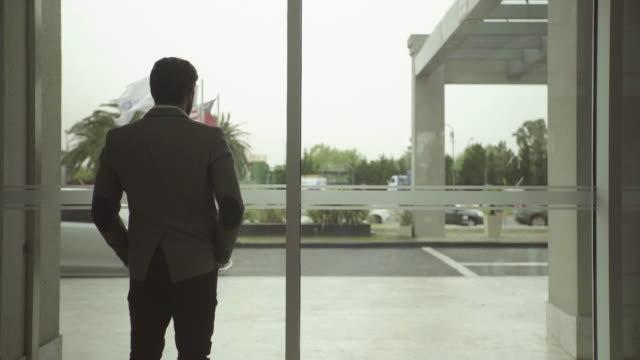 businessman standing with hands in pockets looking out window - hands in pockets stock videos & royalty-free footage
