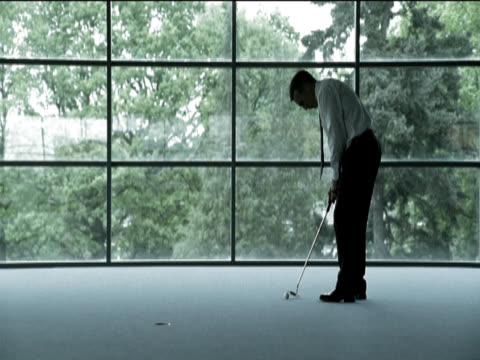businessman stands in an office building putting the golf ball into a hole in the floor then picking the ball up and walking away - einlochen golf stock-videos und b-roll-filmmaterial