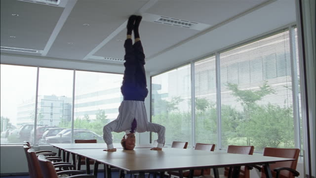 A businessman stands on his head on a conference table.