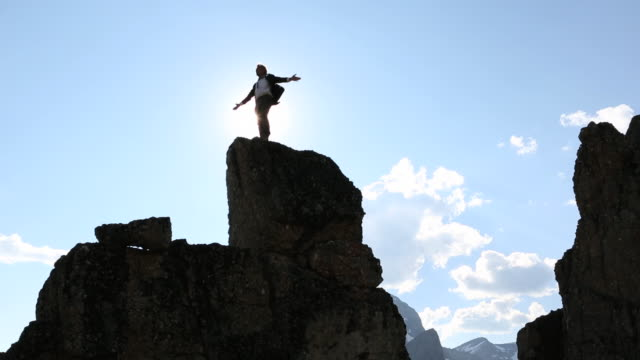businessman stands on top of rock pinnacle, arms out - freedom stock videos & royalty-free footage