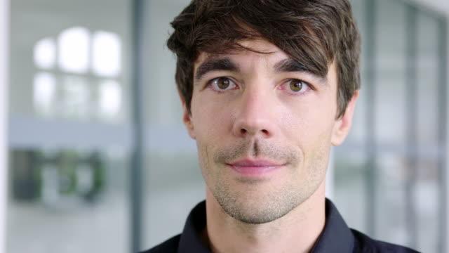 vidéos et rushes de homme d'affaires regardant fixement l'appareil-photo avec un sourire - regarder fixement