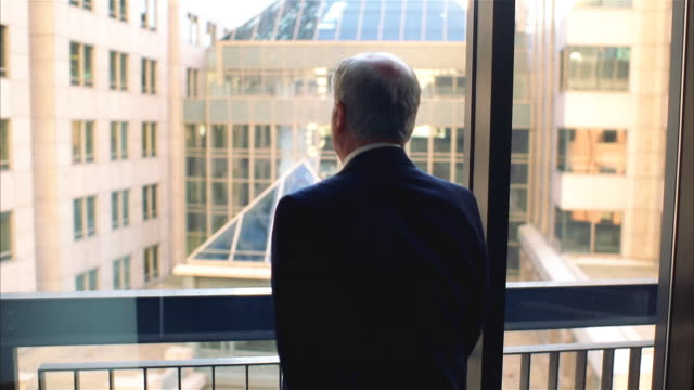 businessman staring out of window at urban view - starren stock-videos und b-roll-filmmaterial