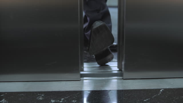 slo mo ds businessman stopping the elevator door with his foot - lift stock videos & royalty-free footage