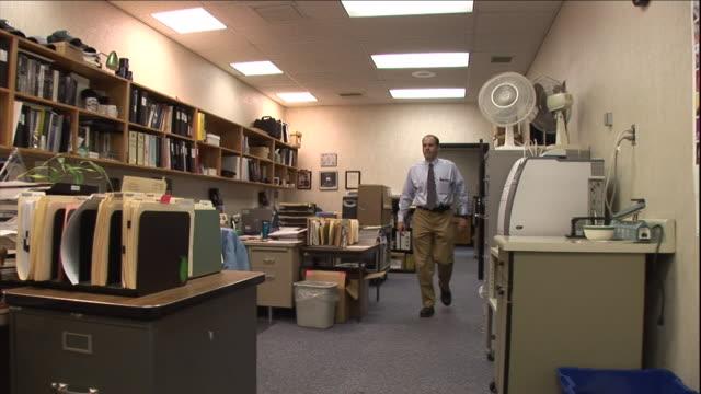 a businessman stops by the desk of a co-worker. - formelle geschäftskleidung stock-videos und b-roll-filmmaterial
