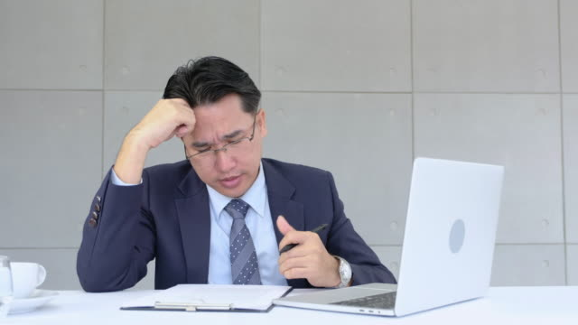 Businessman stressed out about paperwork and data on laptop in modern office