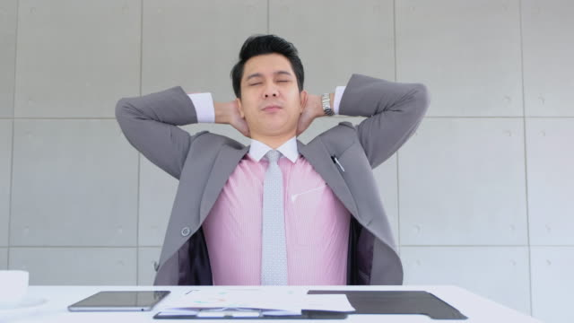 businessman stretching arm up after long working with paperwork on table in modern office