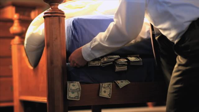 cu businessman stuffing money under mattress, appleton, wisconsin, usa - mattress stock videos and b-roll footage