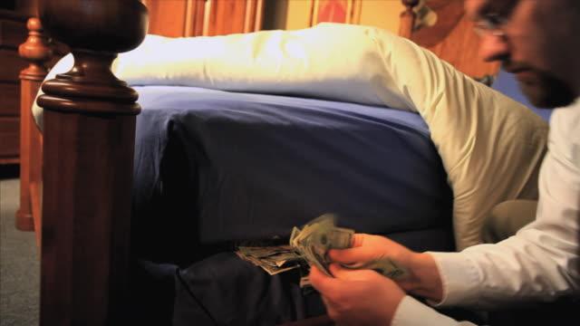 cu businessman stuffing money under mattress, appleton, wisconsin, usa - ウィスコンシン州アップルトン点の映像素材/bロール