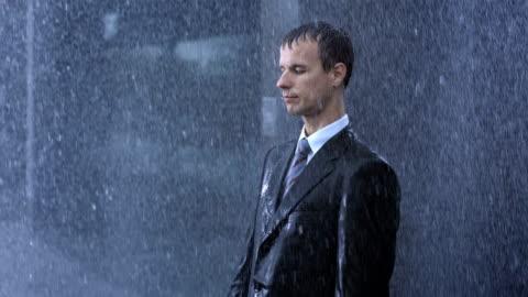 vidéos et rushes de homme d'affaires de vous abandonner à la pluie - glacé