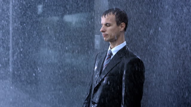 businessman surrendering to the rain - solitude stock videos & royalty-free footage