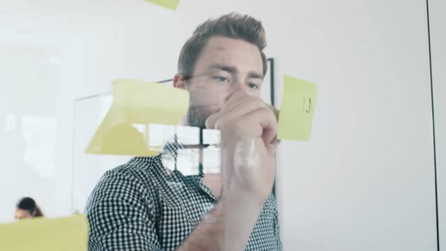 businessman take a planning and appointment on sticky notes attached to glass wall - positioning stock videos & royalty-free footage
