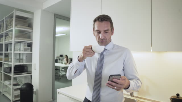 Businessman takes a coffee break in creative, stylish office kitchen