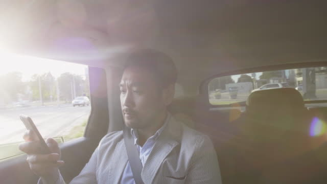 Businessman takes an Uber ride through the city while using smart phone
