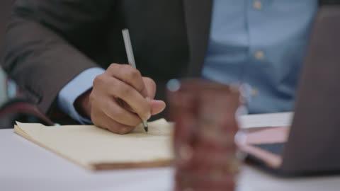 cu businessman takes down notes during a meeting - journalist bildbanksvideor och videomaterial från bakom kulisserna