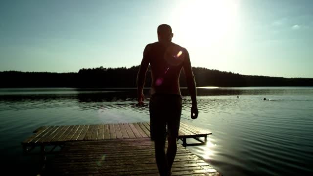 Businessman takes off his suit. Enjoying lake sunset.