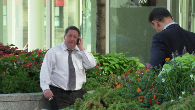ms businessman taking cigarette break and talking on cell phone / boston, massachusetts, usa - quarantenne video stock e b–roll