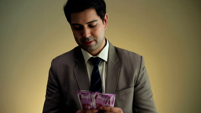 Businessman taking indian two thousand  banknotes in his pocket, Delhi, India