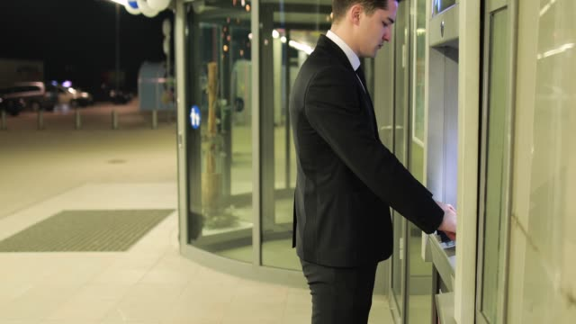 Businessman Taking Payment Out Of ATM
