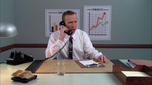 ms businessman taking phone call and appearing shocked/ man crying and putting head down/ new york city - skjorta och slips bildbanksvideor och videomaterial från bakom kulisserna